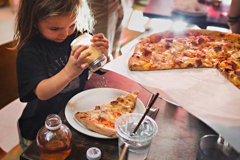 shaking parmesan on pizza